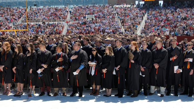 Graduating students rise as the national anthem is performed at the 2017 Iowa State University graduation commencement ceremony. The 2017 class is the largest ever for the university, with over 5,000 students earning degrees.