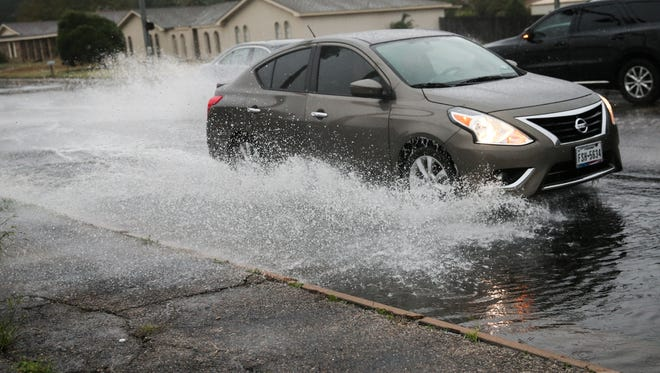 Cars splash up water on Sunset Drive during a rainstorm.