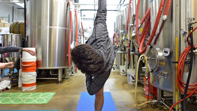 """Francisco Kuljevan from Spring Garden Township balances during the second """"Poses & Pints"""" event on Thursday, Dec. 14 at Collusion Tap Works. The 45-minute Vinyasa flow yoga class, in Collusion's brewing area, was taught by Jenna Ritter from Evolution Power Yoga."""