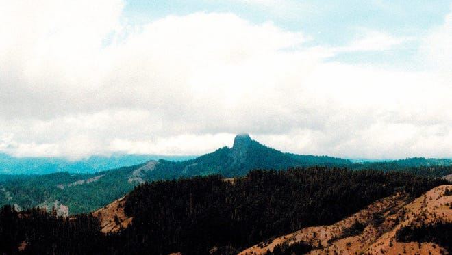 In this July 6, 2000, photo, Pilot Rock rises into the clouds in Cascade-Siskiyou National Monument near Lincoln, Ore. The monument was among those included in the Trump administration's review. (AP Photo/Jeff Barnard, File)