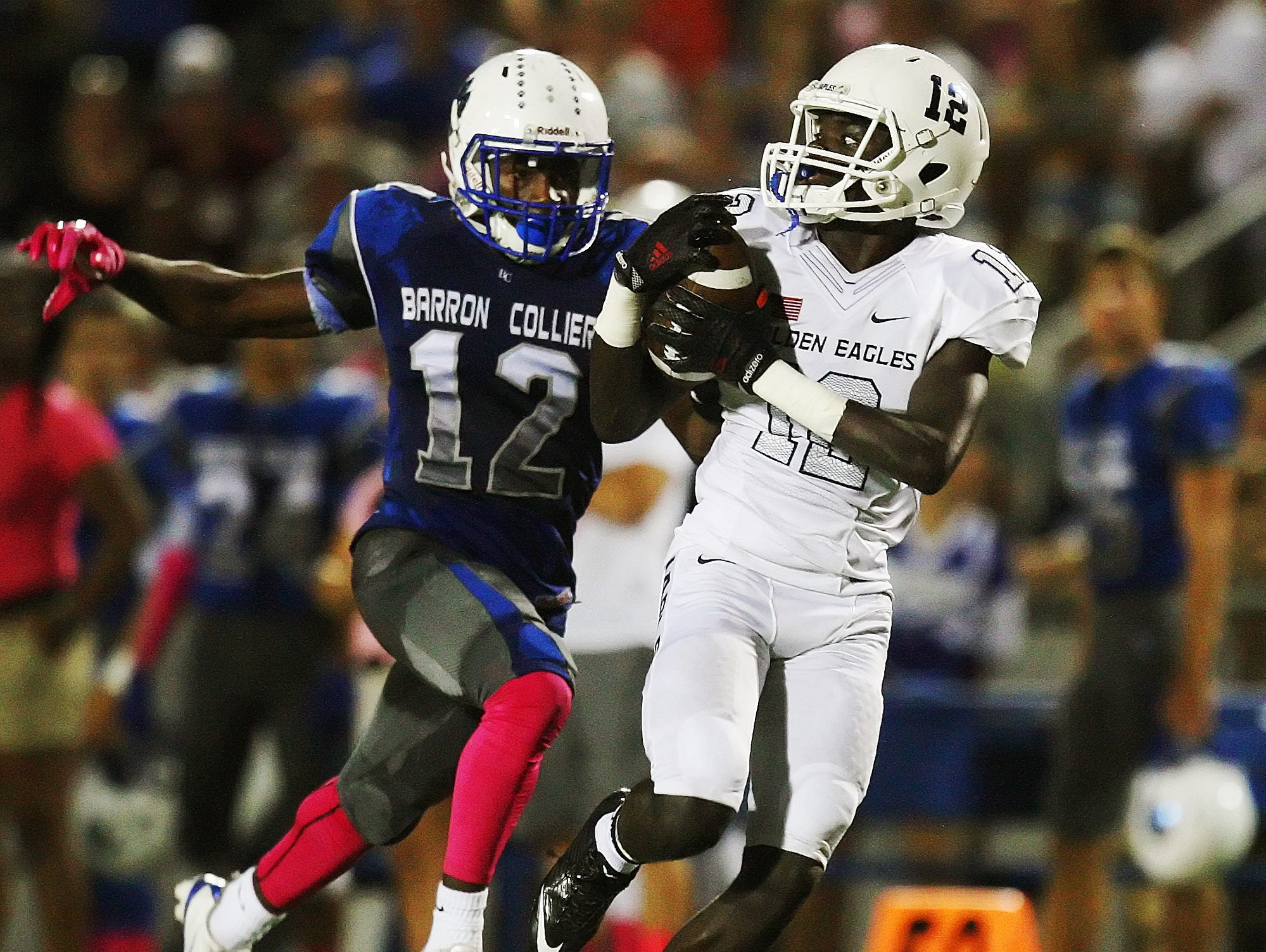 Naples High School's Woody Theork catches a pass against Barron Collier's Dana Brown on Friday at Barron Collier High School in Naples. Naples beat Barron Collier 48-14.