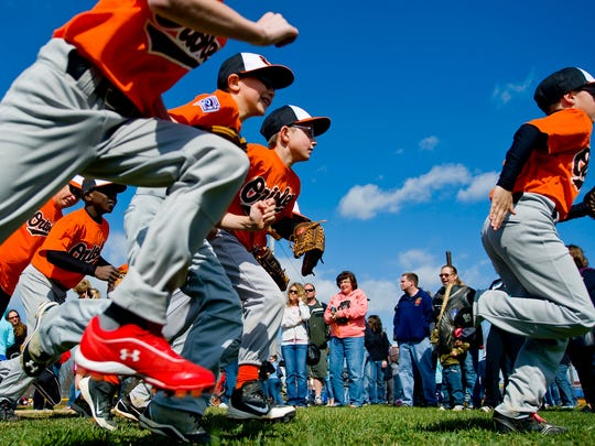 The La Cucina Restaurant-sponsored Orioles team runs out for player introductions during Opening Day festivities for the newly formed Hanover Little League at Pleasant Hill Volunteer Fire Company in April 2013.