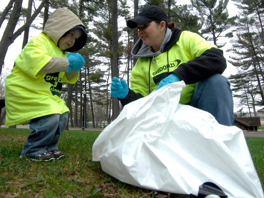 In this file photo volunteers Season Schmitz, right, and her 4-year-old son Isaac, both of Ringle, pick trash during the 2010 Ghidorzi Green and Clean event.