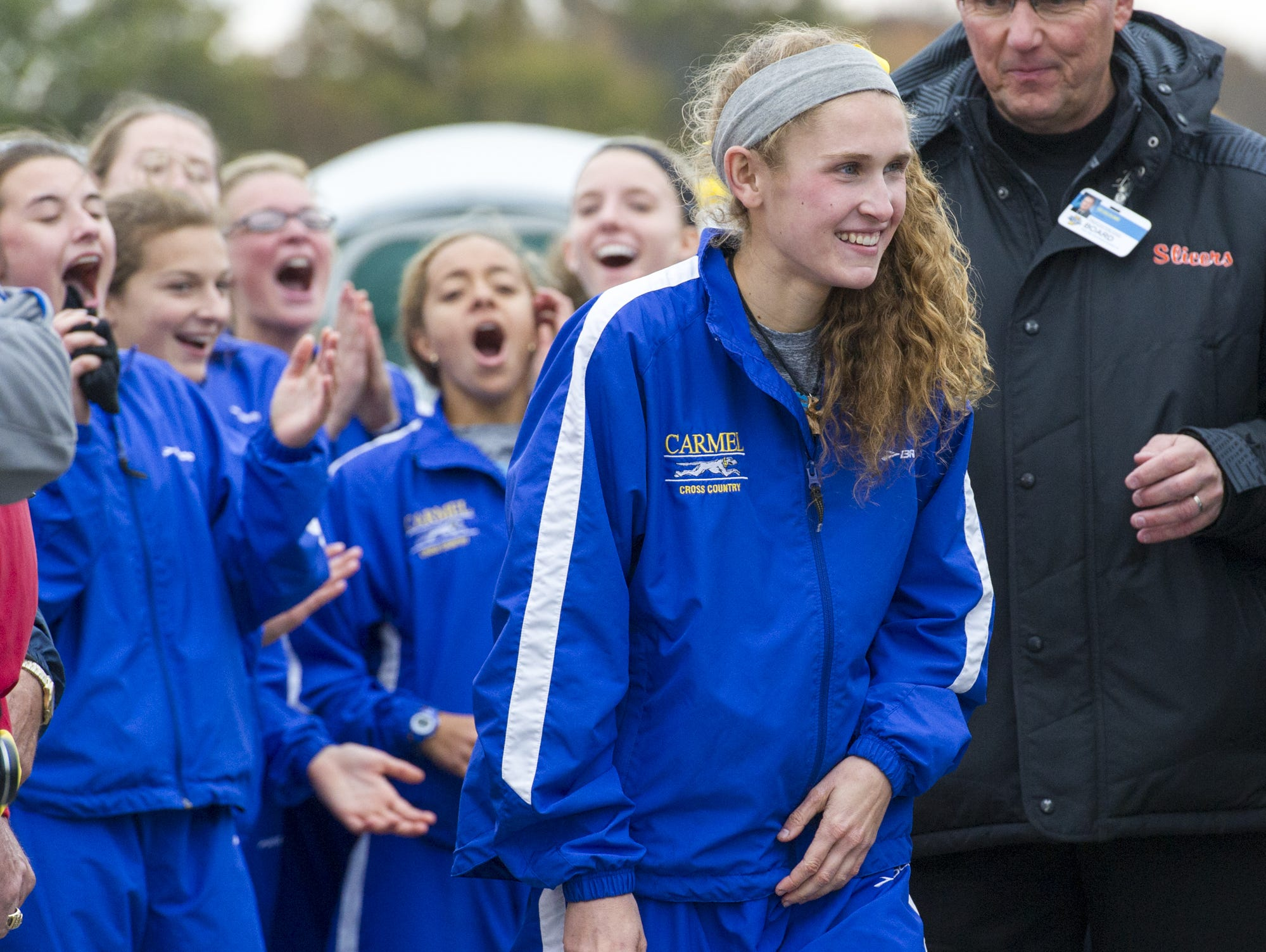 As her teammates cheer for her in the background, Carmel's Sarah Leinheiser is announced as the winner of the IHSAA Cross Country State Championship race in Terre Haute, Oct. 31, 2015.