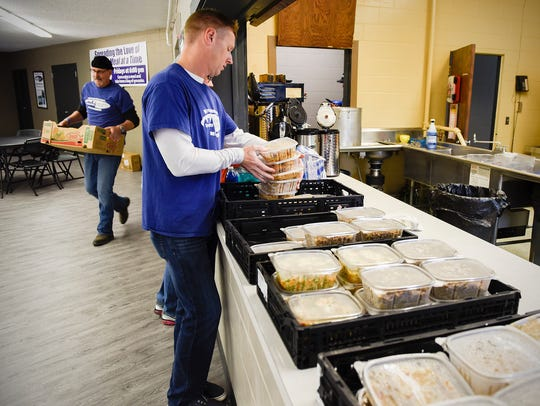 Brian Leitza and volunteers box food and load it into
