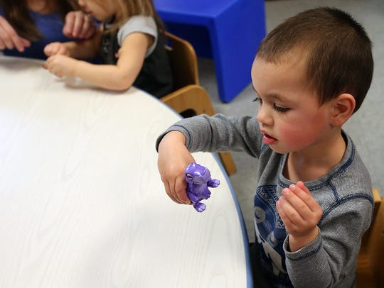 Richie Haswell, 2, looks over a wind-up dinosaur while