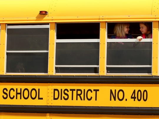 Students peek outside the window of a bus as it prepares to depart from Poulsbo Elementary on Wednesday. An app called Here Comes the Bus tracks the locations of buses along their routes and is in use at North Kitsap and Bainbridge Island school districts.