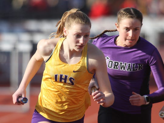 Indianola's Haylee Heuton and Norwalk's Annie Balk break from the starting line in the 4x800-meter relay. The Simpson College High School Classic was held March 26 in Indianola.