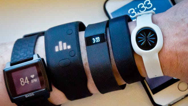 Fitness trackers, from left, Basis Peak, Adidas Fit Smart, Fitbit Charge, Sony SmartBand, and Jawbone Move, are posed for a photo next to an iPhone, on Dec. 15.