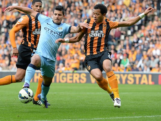 Manchester City's Sergio Aguero, left, and Hull City's Liam Rosenior battle for the ball  during  their English Premier League match at the KC Stadium, Hull England Saturday Sept. 27, 2014. (AP Photo/Anna Gowthorpe/PA) UNITED KINGDOM OUT