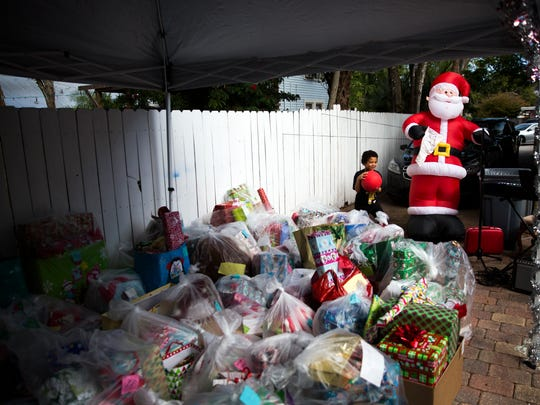 Soldier Morse, 7, runs to catch a ball near the donated presents for over 100 children during the first holiday party at Valerie's House in Fort Myers on Saturday, December 17, 2016. Valerie's House, which opened in January, provides a platform for the community to come together, grieve and openly talk about losing a loved one.