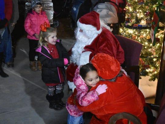 Sophia Fresquez, 6, hugs Mrs. Claus during the Christmas