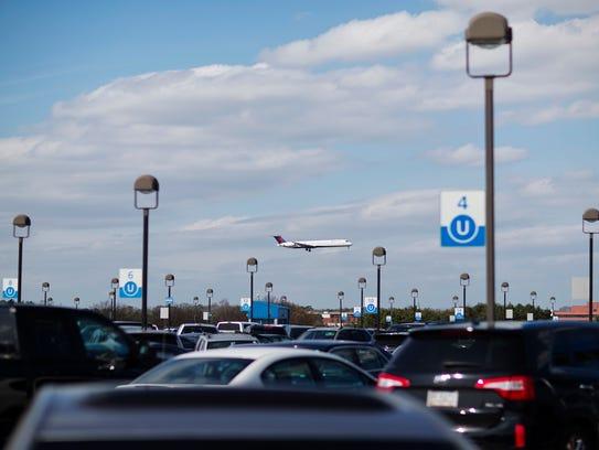 A plane descends over a parking deck at Hartsfield-Jackson