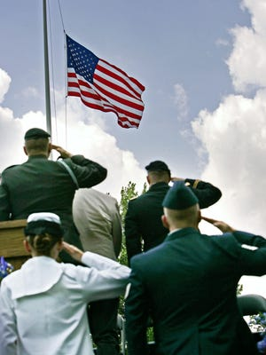 Members of the armed forced salute as the American flag is lowered to half-staff to memorialize those who have died in battle, during Crown Hill's Memorial Service, Monday, May 31, 2010,  as part of Crown Hill's Memorial Day ceremonies.  (Kelly Wilkinson / The Star) <b>06/01/2010 - A13 - MAIN - 2ND - THE INDIANAPOLIS STAR</b><br />Ceremonial: Members of the U.S. armed forces saluted as an American flag was lowered to half-staff at Crown Hill Cemetery during a Memorial Day service Monday.