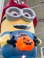 A Minion fireman offers a lighted pumpkin at Lowe's.