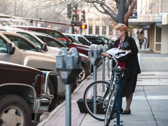 Carrie Koppy feeds a parking meter in downtown Great Falls.