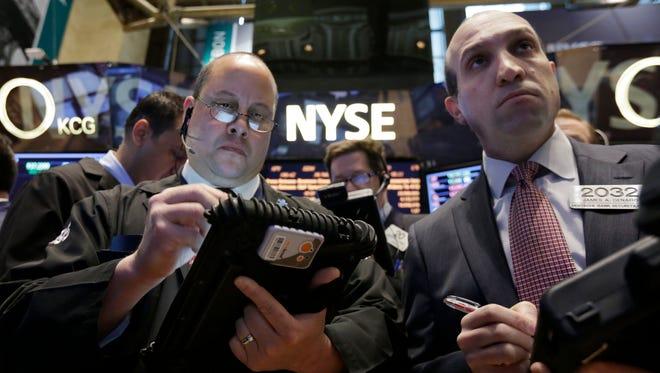 Traders Jeffrey Vazquez, left, and James Denaro work on the floor of the New York Stock Exchange on March 12.