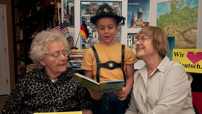 "Friends of the German Language members Christine Conway, left, Tiegan Jordan, 10, and Ingrid Luchini gather as Tiegan reads a German book titled ""Die Olchis fliegen in die Schule"" which translates to ""The Olchis Fly to School."""