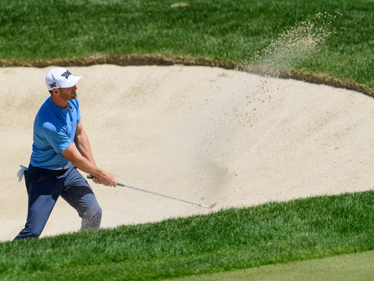 Wyndham Clark hits his ball out of a sand trap on the