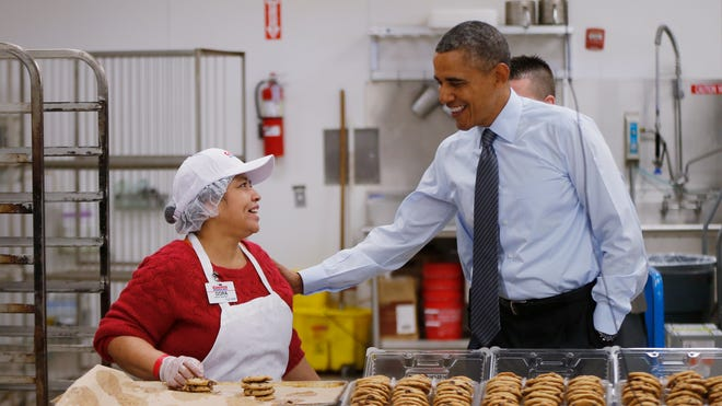 President Obama talks with Dora Martinez, a baker at a Costco store in Lanham, Md., before he spoke about raising the minimum wage Wednesday, the morning after his State of the Union Address.
