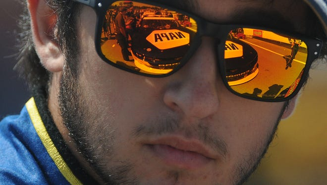 Chase Elliott's NAPA Autoparts Chevrolet is reflected in his sunglasses as he waits for the start of Saturday's race.