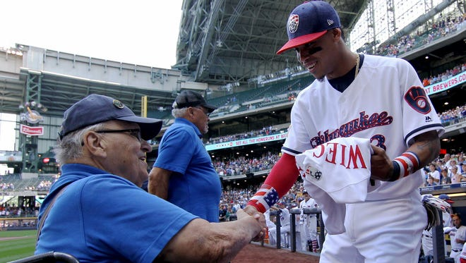 Brewers shortstop Orlando Arcia presents Korean War veteran Don Wiegand with a uniform before the July 4 game against the Baltimore Orioles at Miller Park.