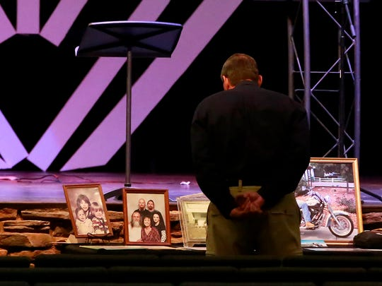 A mourner looks at photos of Everett Griffith before the start of his memorial on Saturday at Pinon Hills Community Church in Farmington.