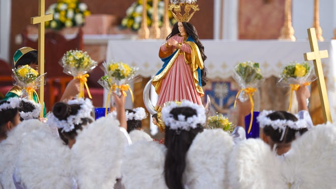 Children, dressed as angels and archangels, offer up miniature floral arrangements to a Santa Marian Kamalen statue during a nobena held at the Dulce Nombre de Maria Cathedral-Basilica on Dec. 8, 2016. The annual Immaculate Conception of the Blessed Virgin Mary was celebrated with a procession of the island's Catholic faithful and others, parading through the downtown streets of Hagåtña.