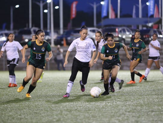 FC Familia's Erica Duenas (in white) tries to keep