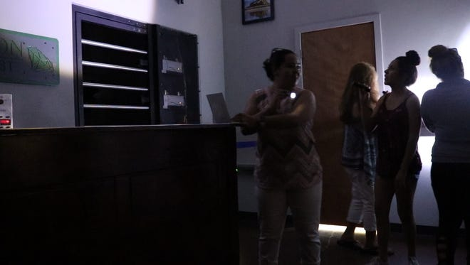 Kayla Garcia, Alexis Garcia, Laura Robertson and Sonya Garcia each search with flashlights for clues in the Tiger's Eye escape room at ConTRAPtions Escape Rooms in Fort Collins on Saturday, July 21, 2018.