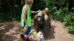 A child touches the head of a gorilla statue where