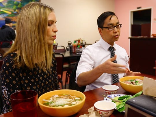 Long Lo, right, and his colleague Angie Wells, give an overview of how to eat pho.