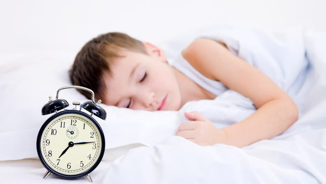 Little boy sleeping with alarm clock