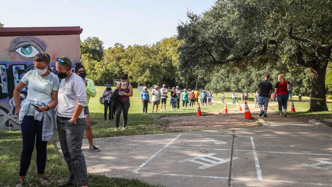 People wait in a long line to vote at an early voting location at the Dittmar Recreation Center in South Austin on October 13.