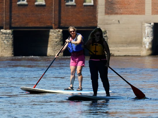 SUP the Rapids owner Kim Kinsey and reporter Caitlin Shuda paddleboard under Jackson Street Bridge near Verso.