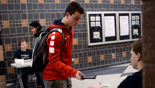 """Casey Coltrin, 15, of Lake Orion, hands his cell phone to a fellow student during the """"Cell Out for Soldiers"""" event on Friday, Jan. 13, 2017 at Lake Orion High School in Lake Orion."""