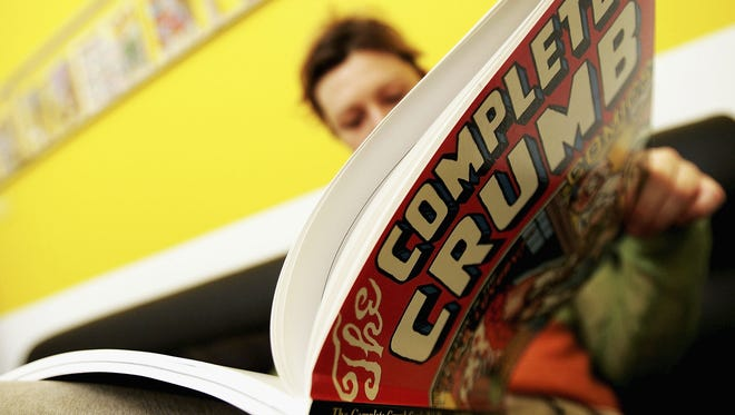 FILE - A woman reads a comic book in London.