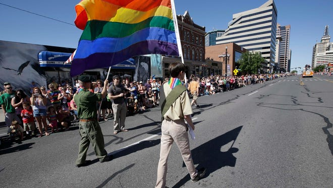 FILE - In this June 8, 2014, file photo, a group of Boy Scouts march during the Salt Lake City's annual gay pride parade in Salt Lake City. An announcement Tuesday night, May 8, 2018, by The Church of Jesus Christ of Latter-day Saints and Boy Scouts will mark an end to close relationship that lasted more than a century built on their shared values. The religion will move its remaining boys into its own scouting-type program. (AP Photo/Rick Bowmer, File)