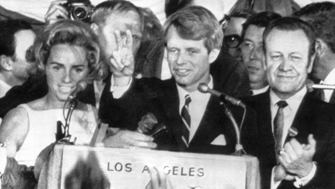 U.S. Sen. Robert F. Kennedy holds two fingers up in a victory sign as he talks to campaign workers at the Ambassador Hotel in Los Angeles, Ca., June 5, 1968.  He is flanked by his wife Ethel, left, and his  campaign manager, Jesse Unruh, speaker of the Calif. Assembly. After making the speech, Kennedy left the platform and was assassinated in an adjacent room.