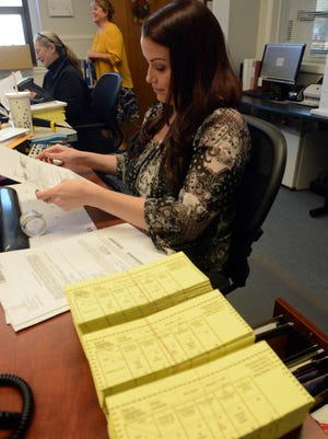 Kelsey Shaver, assistant Killingly town clerk works by three piles of election ballots Wednesday at the Killingly Town Hall.