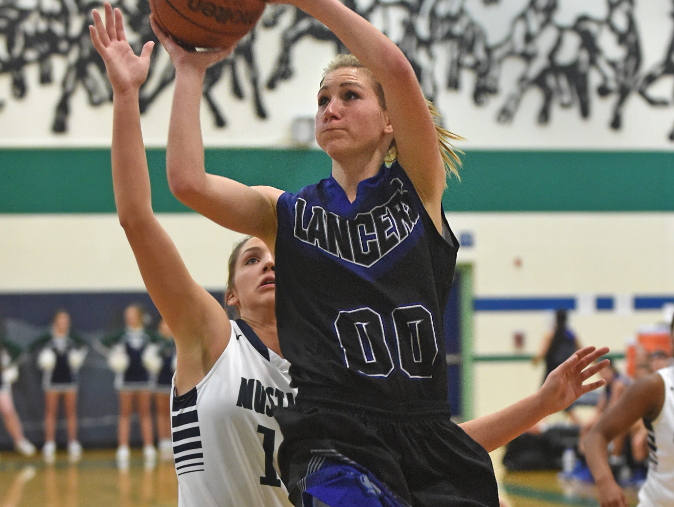 McQueen sophomore Izzy Warren goes up to score with Damonte's Morgan Waller covering her in Tuesday's game at Damonte Ranch High School on Dec. 1, 2015.
