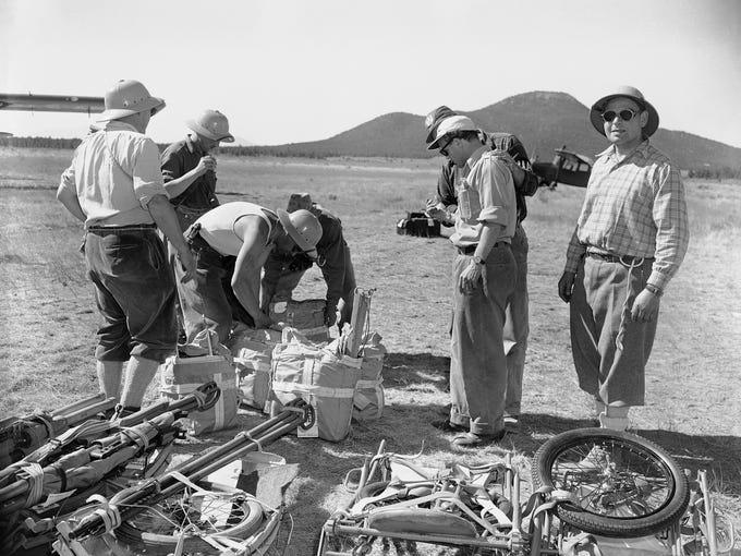 Members of a Swiss mountain climbing team sort equipment