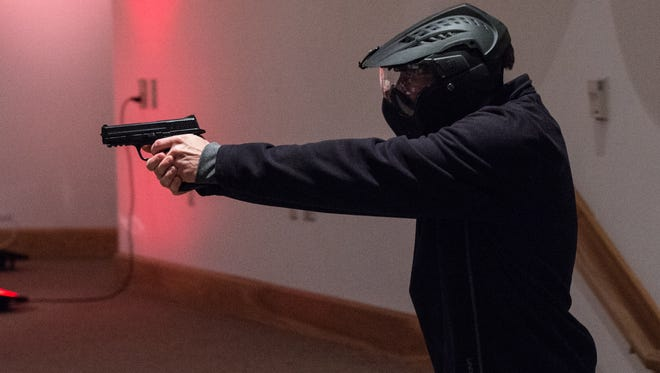 A Wicomico County Sheriff's deputy role plays as an active shooter during a training and presentation at Allen Memorial Baptist Church on Wednesday, Dec. 13, 2017.