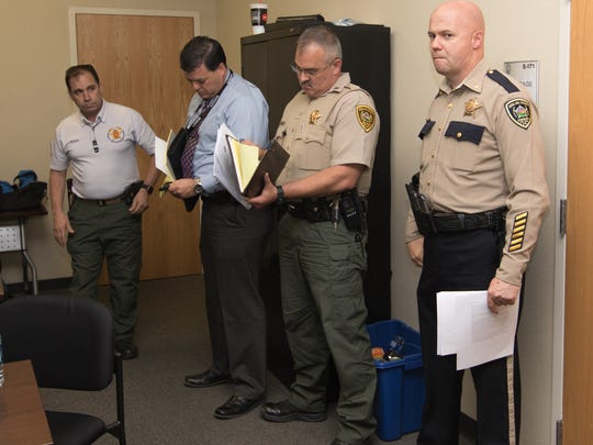 Members of Doña Ana County Sheriff Department Command, including Major Brent Barlow, right, await the start of a news conference Tuesday, April 26, 2016, at DASO headquarters
