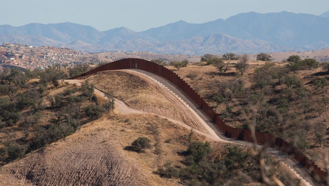 The border fence stretches west of Nogales into the Coronado National Forest.