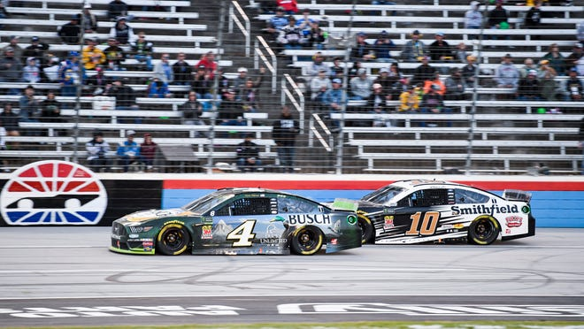 FILE - In this Nov. 3, 2019, file photo, Kevin Harvick (4) and Aric Almirola (10) battle for position during a NASCAR Cup Series auto race at Texas Motor Speedway, in Fort Worth, Texas. The massive grandstands at Texas Motor Speedway stretch about 2/3 of a mile long, and were empty for the last race there. There could still be some feeling of emptiness Sunday, preferable for social distancing, even when the NASCAR Cup Series race becomes the first major sporting event in Texas in more than four months to allow spectators. It will be one of the largest gatherings of any kind in the state since the start of the coronavirus pandemic.