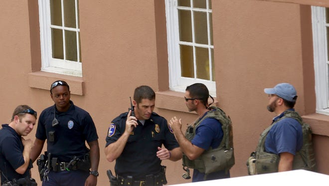Police gather near the scene of a reported shooting in Charleston, S.C., on Thursday, Aug.24, 2017.  Authorities say a disgruntled employee shot one person and is holding hostages in a restaurant in an area that is popular with tourists. Mayor John Tecklenburg said at a news conference that the shooting was not an act of terrorism or racism.