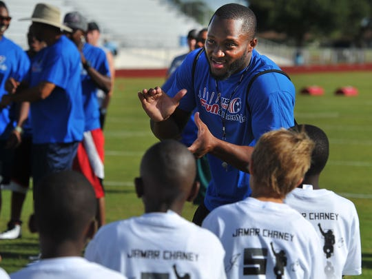 Jamar Chaney, an NFL linebacker for the Philadelphia Eagles, talks with more than 200 students attending his football camp June 16, 2012 at Lawnwood Stadium in Fort Pierce. Chaney, a  St. Lucie West Centennial graduate, returned to Fort Pierce to give back to his community and teach football fundamentals along with several of his NFL friends during the free clinic.