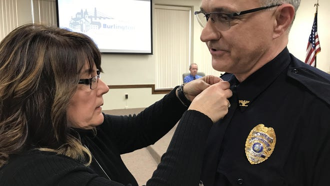 Burlington Police Chief Dennis Kramer gets his badge and lapel pins on his uniform by his wife, Tami, during the swearing-in ceremony April 16, 2017 at Burlington City Council meeting at city hall.