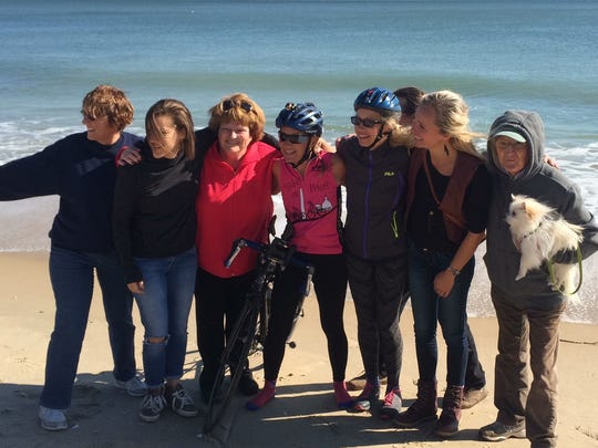 Salvo dipped her bike wheels into the Atlantic at the end of her ride. She had dipped the wheels in the Pacific 59 days earlier. Gathered to celebrate the accomplishment were Connie Whaley (left), Solé Salvo, Susie Schmitt, Lynn Salvo and Elise Greenberg. On the right is Salvo's husband, Giovanni, and their dog, Bebé.